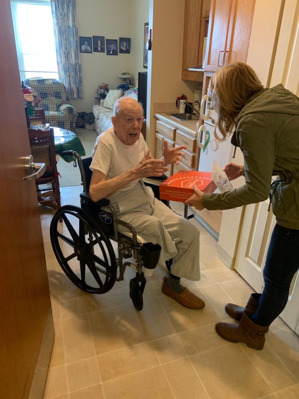 Purpose Founder Holly Masters hand delivering orange Purpose Box to grandpa
