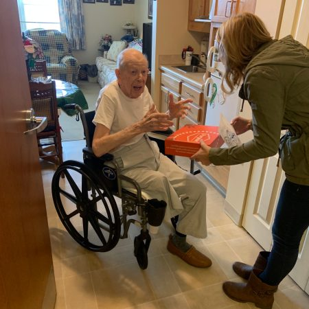 Purpose Founder Holly Masters hand delivering orange Purpose Box to grandpa