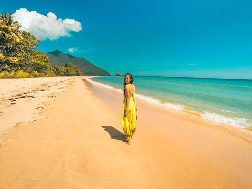 Nanda walking on an uncrowded beach