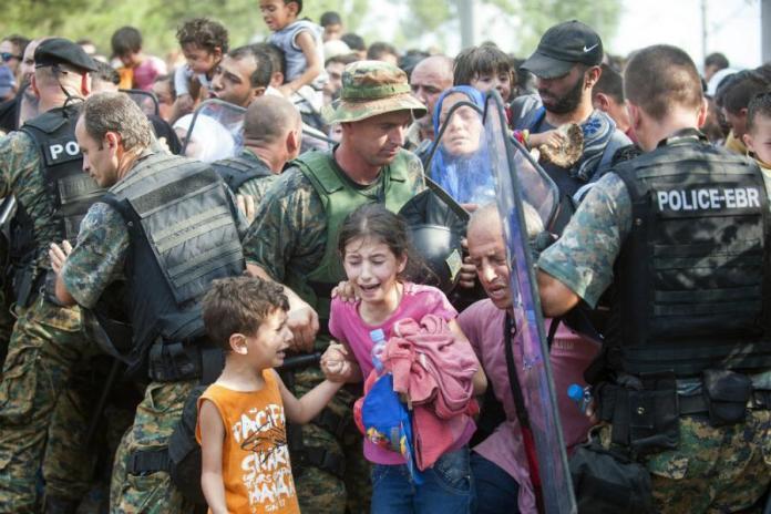 Policija u opremi za razbijanje nemira, koja stoji iza bodljikave žice, ispalila je suzavac u pokušaju da potisne ljude koji žele da prođu kroz Makedoniju.