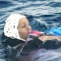Muslimanka pokušava da održi svoje dijete na površini vode nakon utapanja broda koji je prevozio migrante