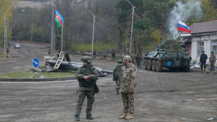 An Azerbaijani service member and a Russian peacekeeper stand guard at a checkpoint on the outskirts of Shusha