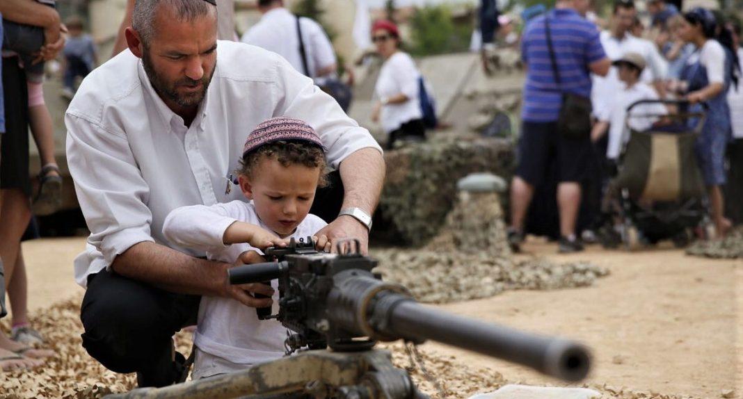 Židovski doseljenik podučava malodobno dijete rukovanju sa vatrenim oružjem. Hiljade ovakvih fotografija ostane