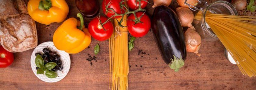 tafel vol met verse groenten en pasta