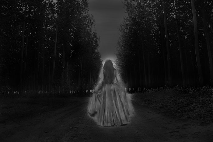 Ghost woman walking through the forest