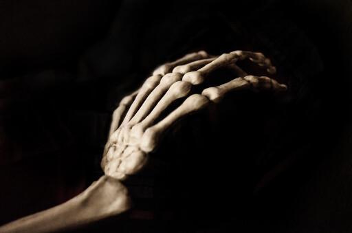 Skeleton hand reaching in the dark