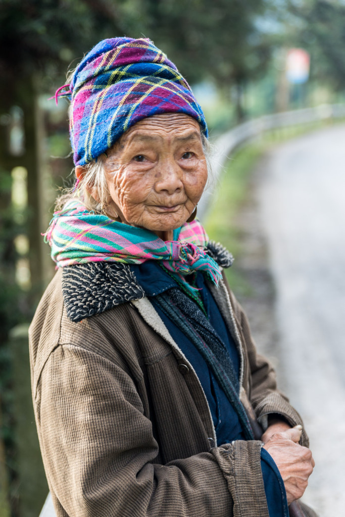 An elderly woman wears the traditional colours of the Flower Hmong hill tribe, outside Sapa, Vietnam.