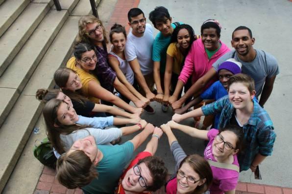 Students make a skin rainbow at the MLK Memorial.