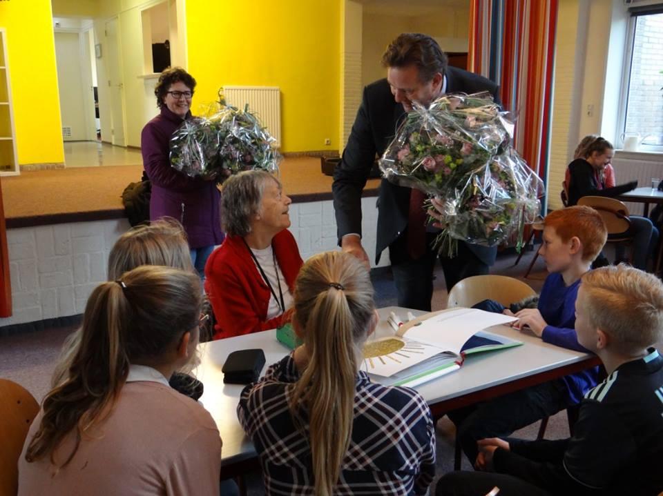 De burgemeester geef tijden een bezoek aan het Scholenproject enkele kinderen een hand.