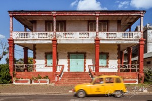 Colonial architecture typical of Diego Suarez (Antsiranana), north of Madagascar, with a typical taxi on october 14, 2016