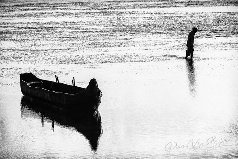 Pirogue et pêcheuse sur le front de mer d'Antalaha, Madagascar