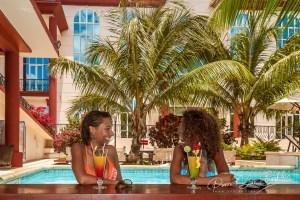 Deux jeunes femmes malgaches dégustant un cocktail au bar de la piscine