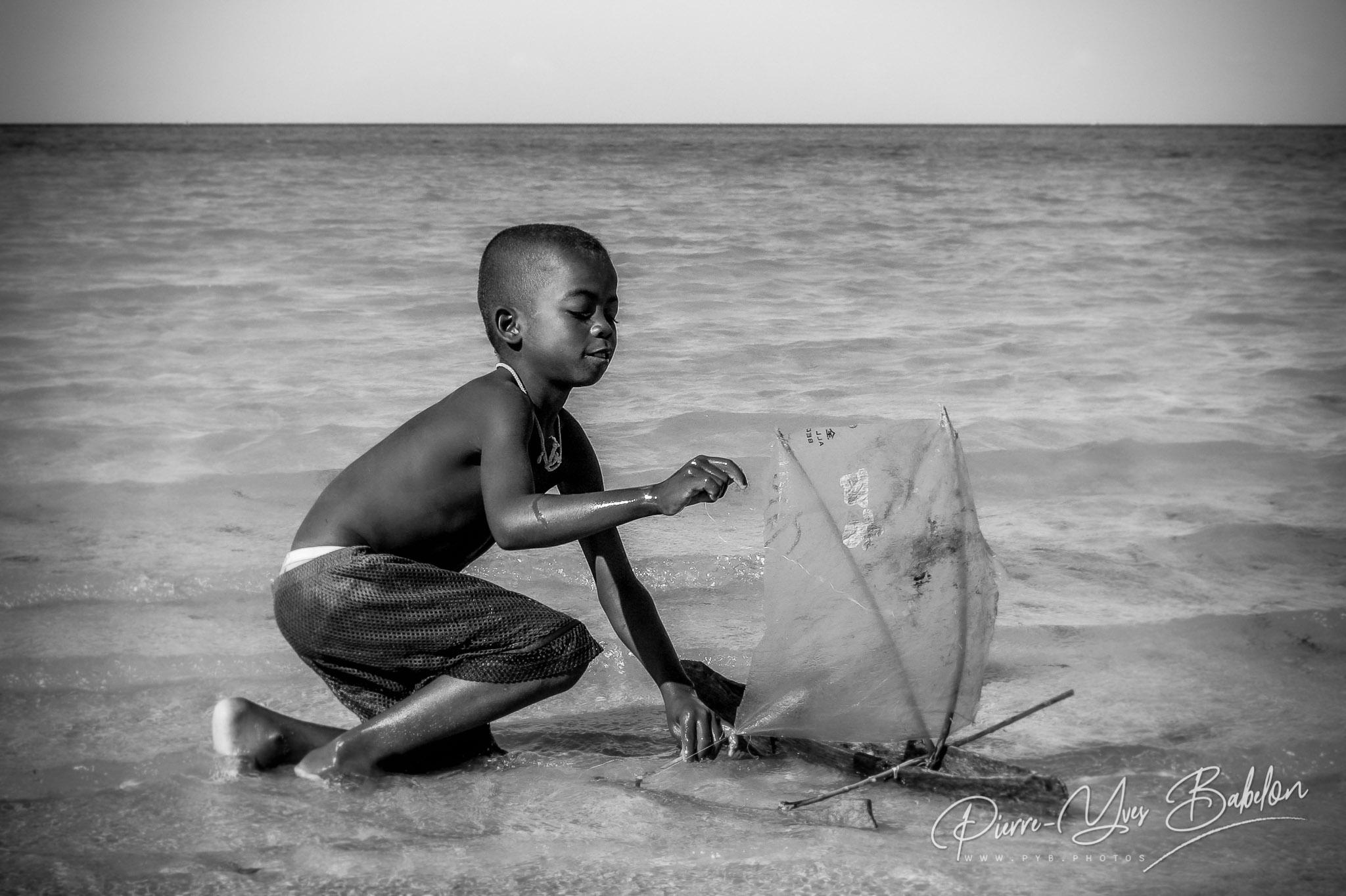Enfant Vezo jouant avec sa pirogue à balancier à Ifaty, Madagascar