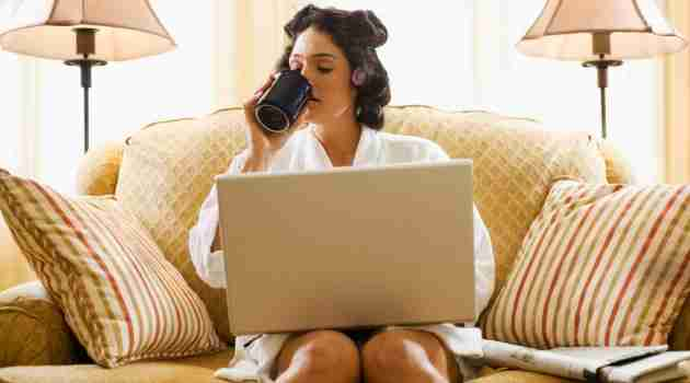Woman in hair curlers working at home with laptop computer
