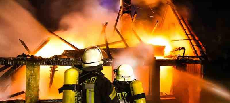 Brennendes Gebäude mit Flammen und Feuerwehrleuten.
