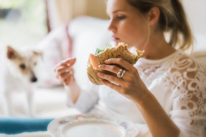la Mujer experimenta la necesidad de comer compulsivamente antes de que el período de tenencia de un sandwich