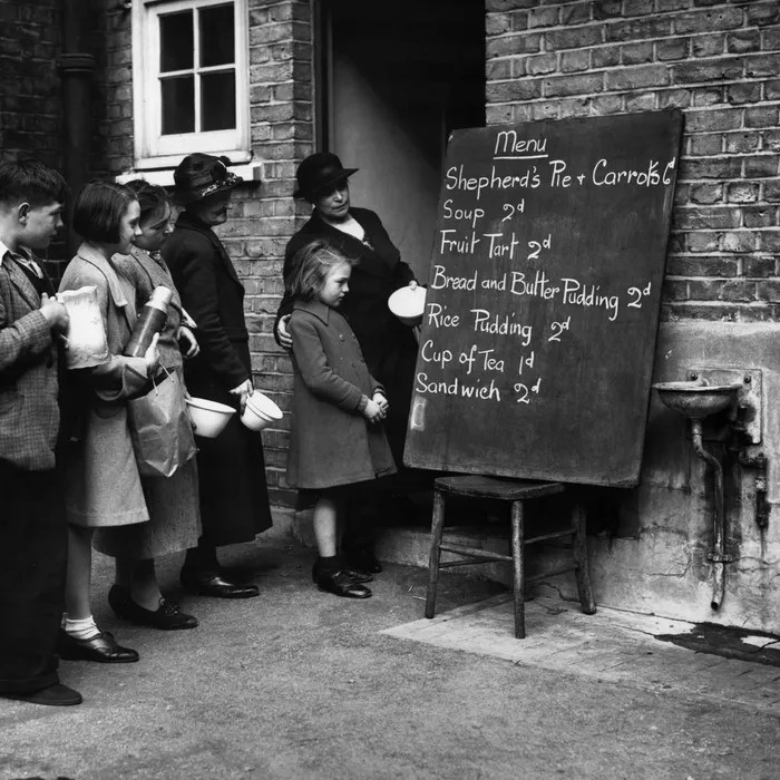 A vintage black-and-white photograph of women and children in a line, looking at a short food menu written on a chalkboard