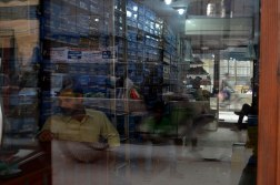 A shopkeeper sits inside his shop while people walk outside