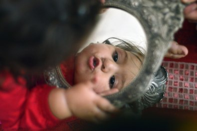 Aaminah, (1 year), looks at herself in a mirror.