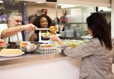 volunteers serving food in shelter