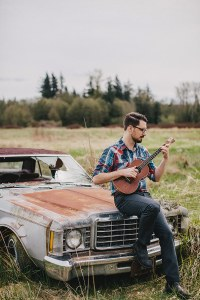 James Hill playing ukulele against a rusty car