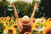 photographie de femme entouree de tournesols