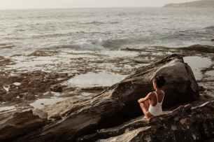 photo de femme assise sur un rocher