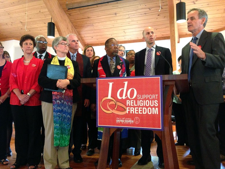Clergy and national officers with the United Church of Christ join with other local clergy and their legal counsel at a press conference announcing their lawsuit on Monday morning.