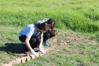 Emily & Larisa reusing bricks from the field as a boundary for the playground.