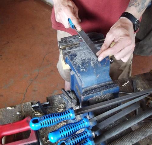 Filing the metal.