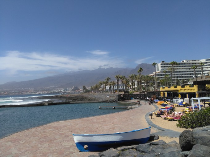 A photo of the beach in Tenerife, with the mountains in the background and a clear blue sky