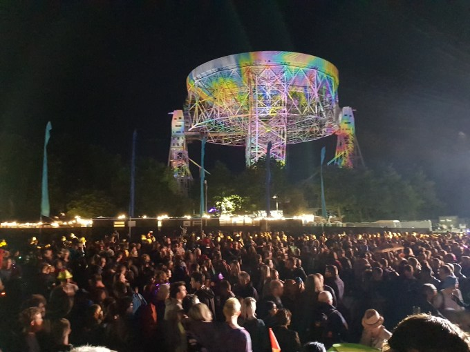 Lots of people standing in the foreground with a large radiotelescope dish in the background illuminated by multicoloured lights