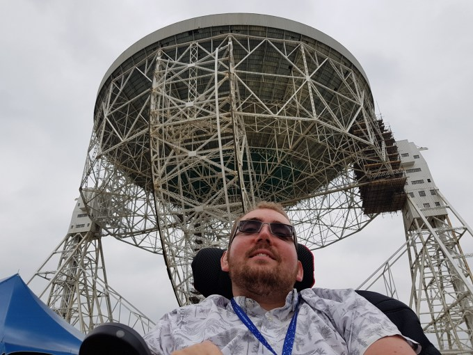 A bearded young man smiles at the camera with a big radiotelescope dish