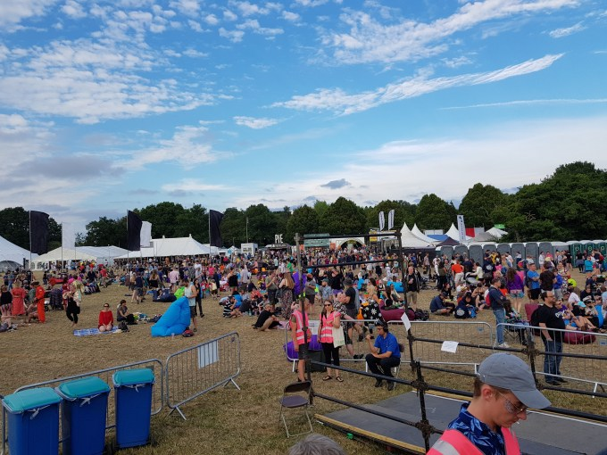 Lots of people are standing on the grass, some are sat on blankets or inflatable cushions. Some tents are in the background where DJs played