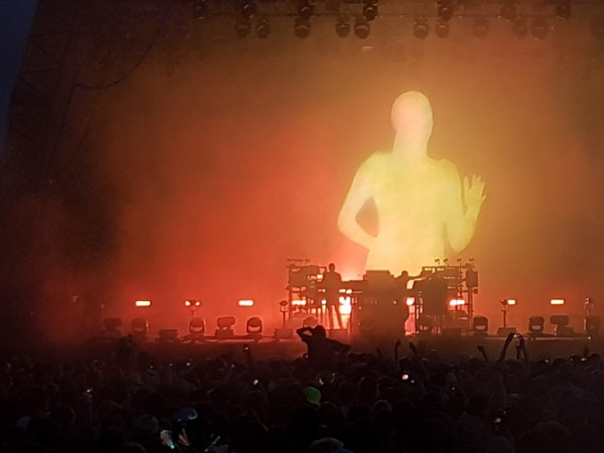 A close-up of the chemical Brothers onstage performing. They are standing behind the decks as a Large silhouette of a woman running is projected onto the screen behind them.