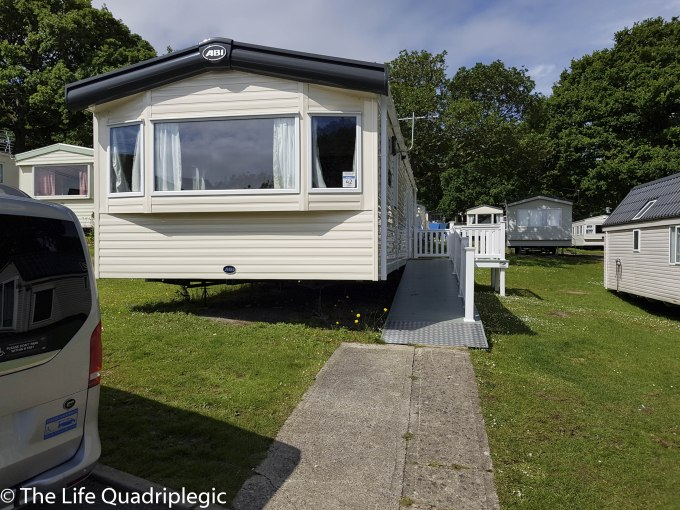 A wheelchair accessible static caravan with a ramp along the side leading up to the front door