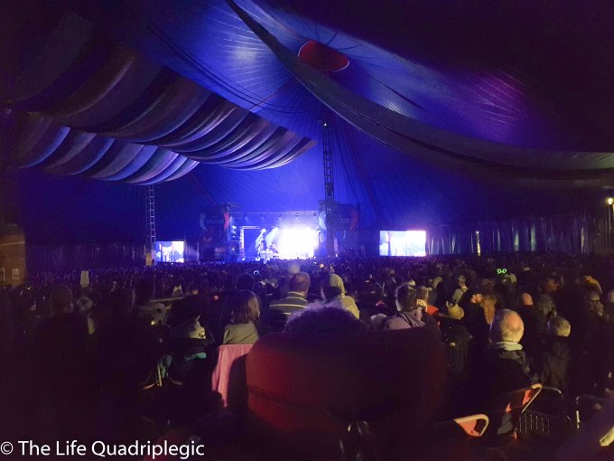 He shot over the top of large crowd, Inside a tent with a stage in the background.