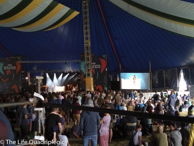 A stage is in the background with a big screen to the right of it. A large crowd is stood in front of the stage watching a band