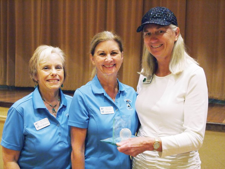 Left to right: Past President Dee Waggoner presents the Coveted Quail to Nancy Resnick for having the lowest net score for the six week period while Vice President Kelly Hines looks on; photo by Sylvia Butler.