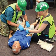 Karl Holmstrom and Rachel Ramsower tend to victim Doug Dorsey's many injuries during a recent CERT training class; photo by John McGee.