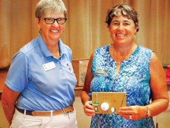 Cathy Thiele congratulates Linda Weissman who is holding the plaque she received for having the Lowest Gross Score between June 15 and August 24; photo by Sylvia Butler