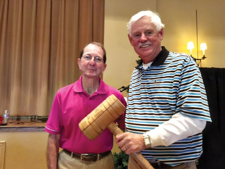 Outgoing President of the QCMGA Skip Fumia passes the gavel to incoming President Tim Phillips at the annual meeting.