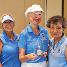 Joyce Walton holds the Crystal Golf Ball plaque flanked by Diane Dodd (left) and Yoshie Hennessy. Each will be able to take the plaque home for three weeks to show it off to family and friends; photo by Sylvia Butler.