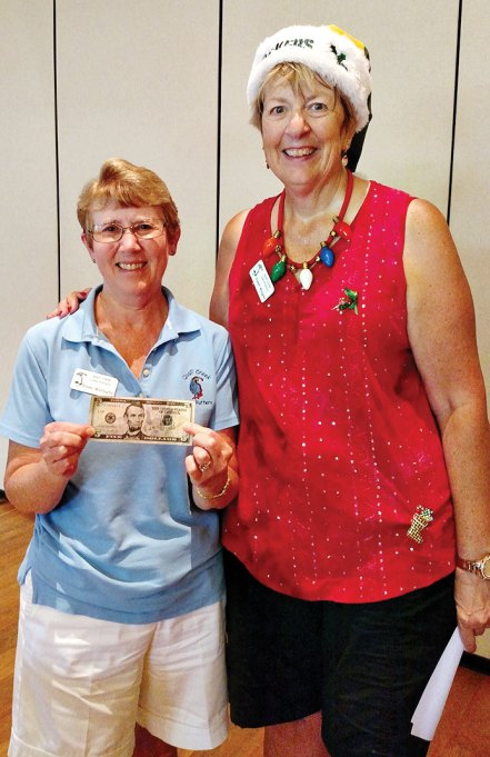 Diane Waldapfel (left) was the lone Putter who got a hole-in-one on the mystery hole on July 11. She earned $5 for her achievement presented by Janet Wegner; Photo by Sylvia Butler.