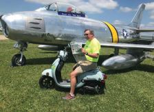 Bill Foraker relaxes in front of an F86 Sabre fighter jet while working the Warbirds area of EAA Oshkosh Airventure 2019.