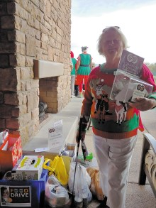 Pam Schroeder holds up the collection jar containing $450 in cash, check, and credit card donations; Photo by Peggy McGee.