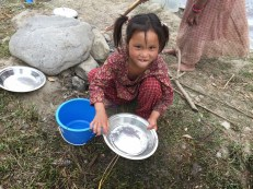 A girl washes dishes in Camp 1