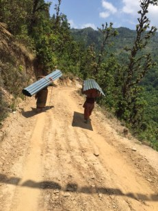 Women carry their roofing sheets home. A large number of men in the village are working in India, Malaysia, Qatar, Korea.