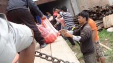 Unloading and storing supplies in Kalikasthan. Prem Tamang, our local coordinator (front), mobilized a huge group of volunteers