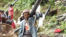 Locals from Khopachagu carry toilet construction supplies to their village